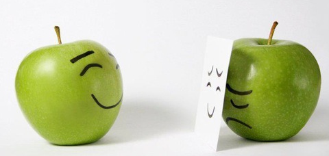 Two apples with drawn faces. One with a fake happy mask